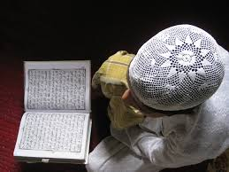 young boy reading the quran